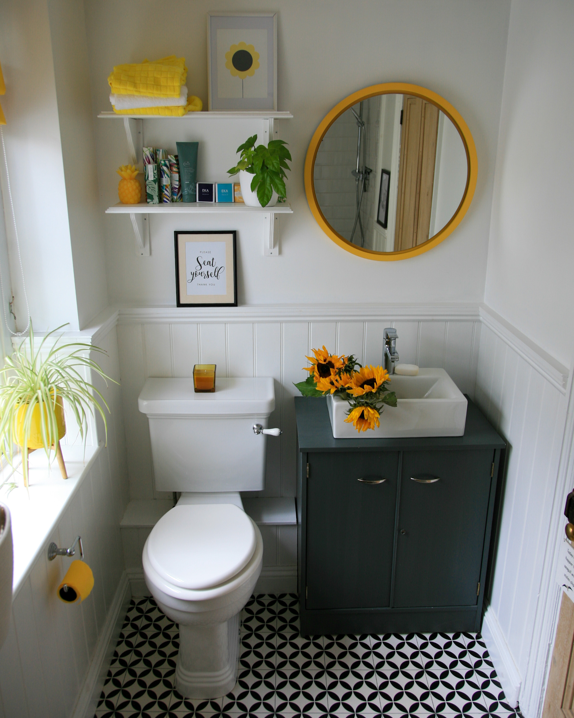 Image shows a sink unit painted in Farrow & Ball Downpipe with sunflowers in the basin. There is a yellow round mirror above the sink and two shelves showing other yellow accessories. Next to the toilet on the window sill there is a house plant in a yellow plant pot.