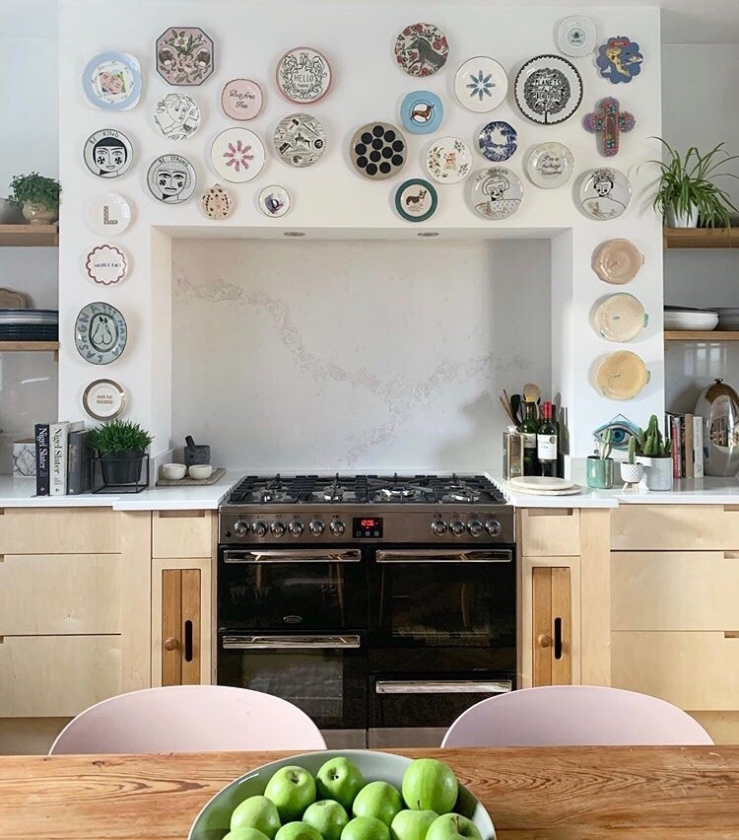 The wall above the oven in the kitchen has been decorated with decorative plates.
