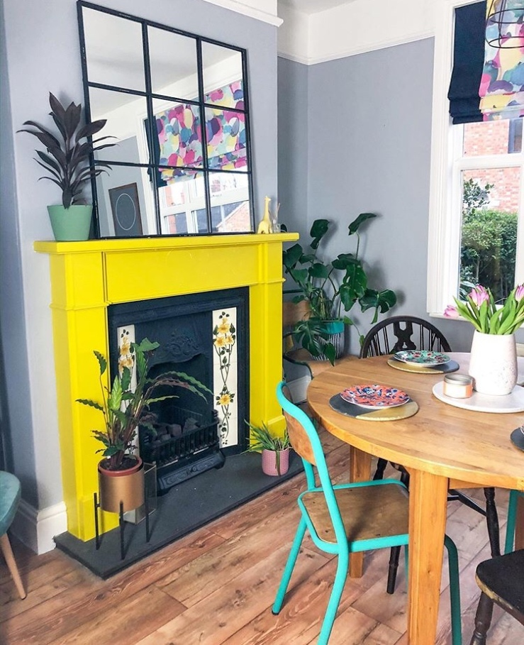 A traditional fireplace has been painted yellow to create a feature in the room.