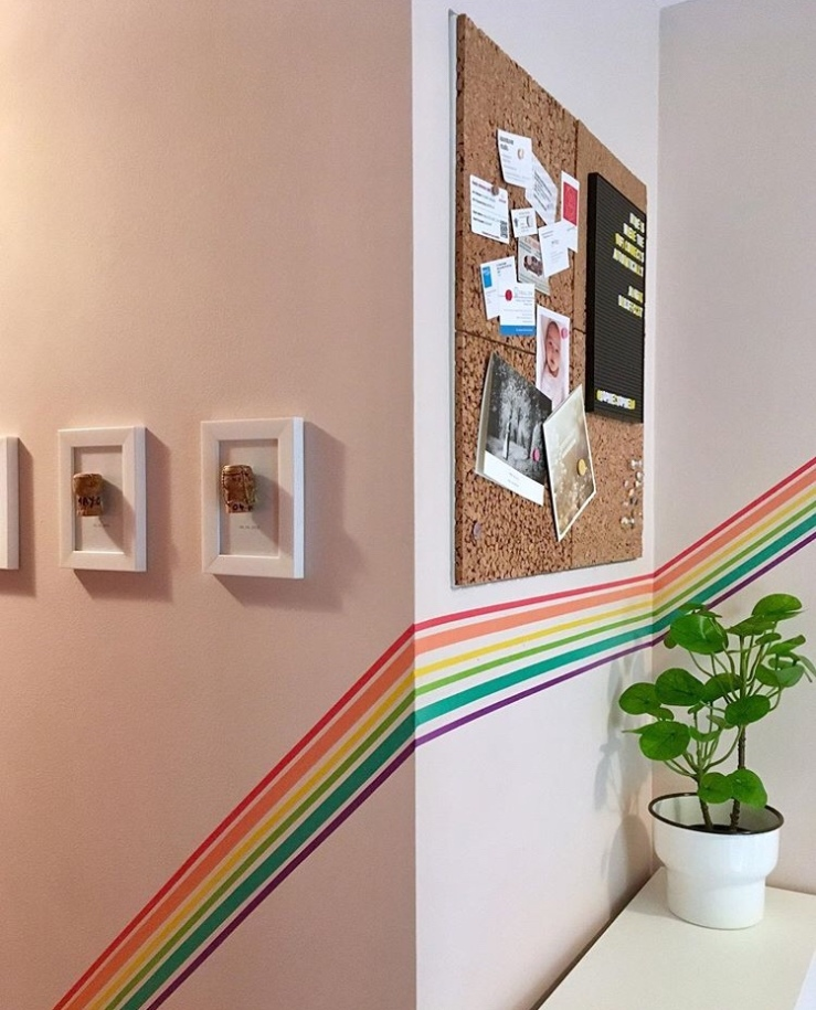 Neutral wall decorated using washi tape to create a rainbow border.