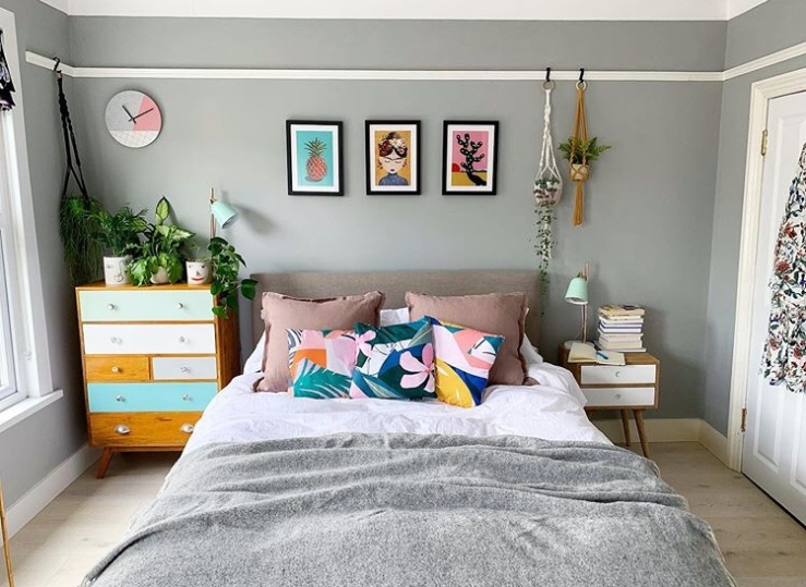 A neutral bedroom has been decorated with brightly painted drawers, colourful artwork and cushion covers.