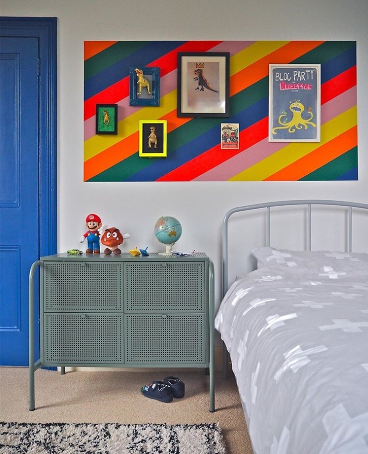 Child's bedroom with a blue painted door and above the bed a striped box has been painted and gallery wall displayed.