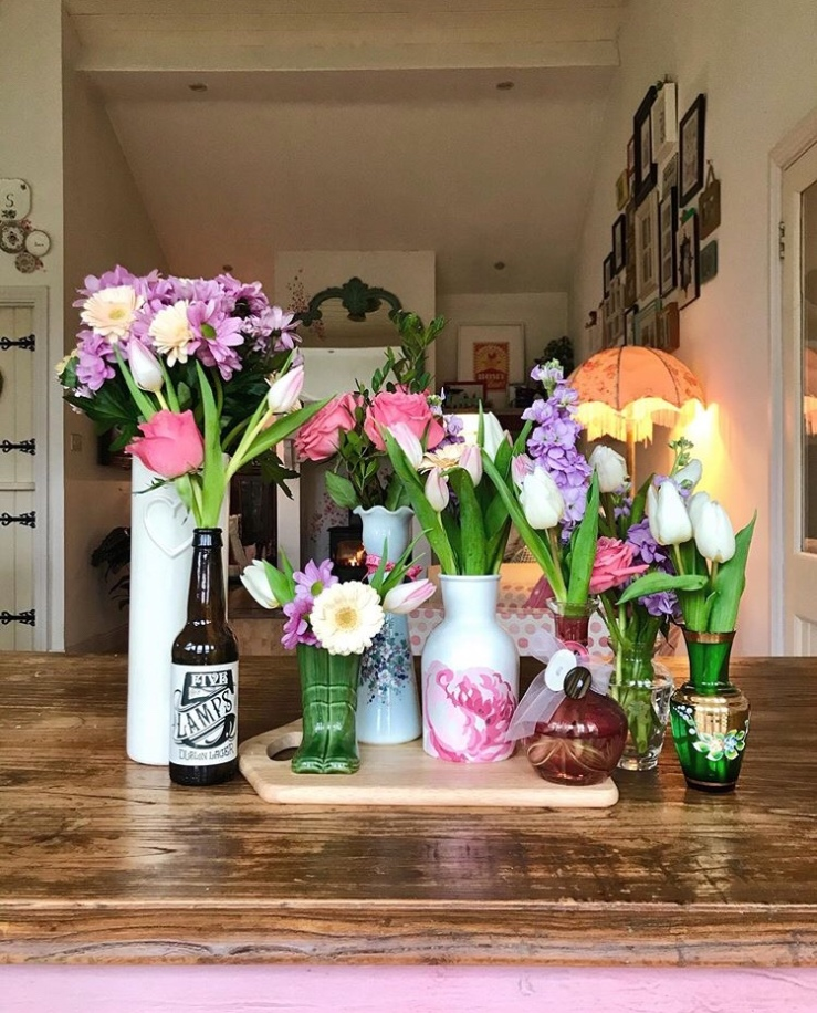 Colourful flowers have been displayed in a variety of colourful vintage vases.