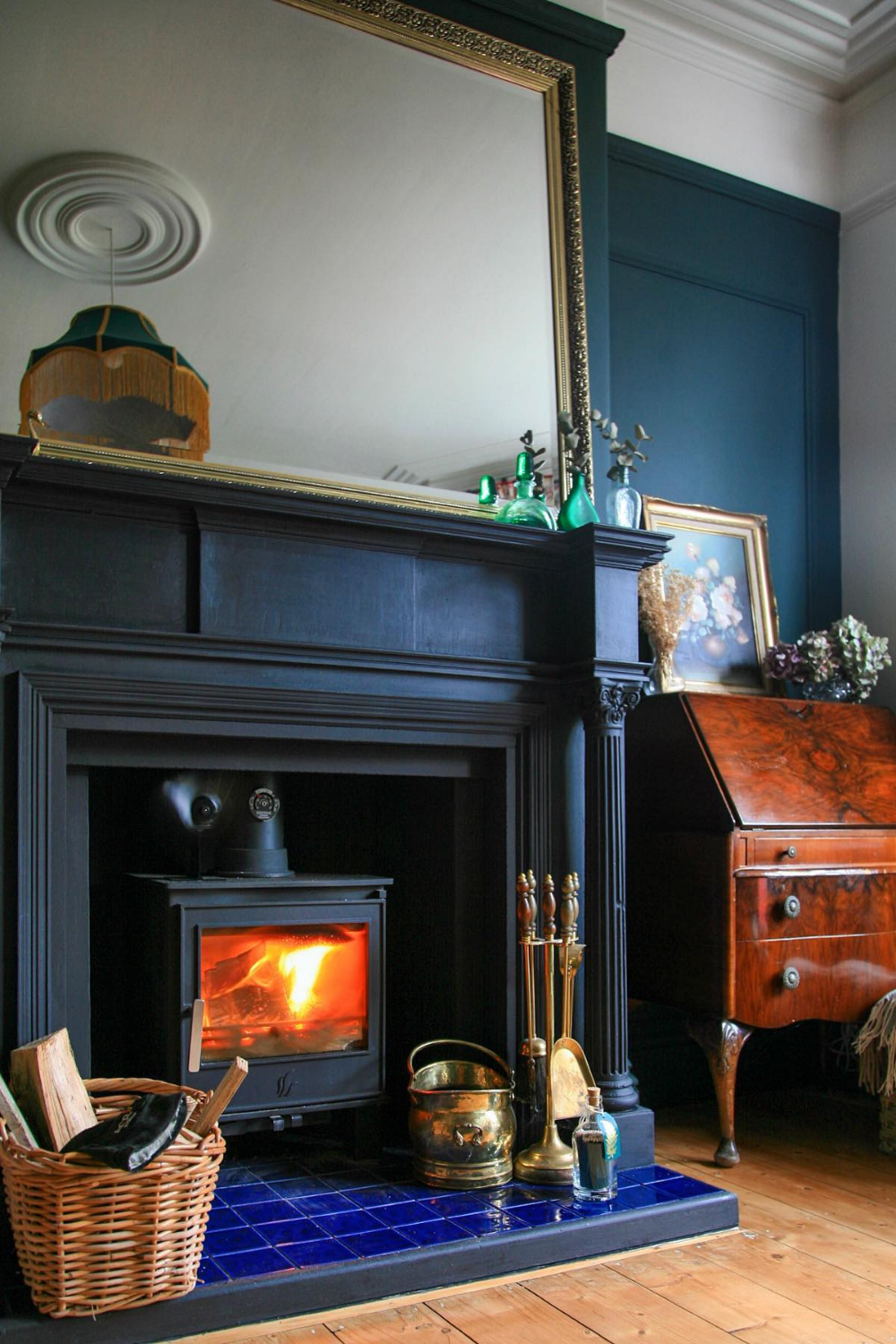 A wood burning stove in a black fireplace with a large gold mirror above it.