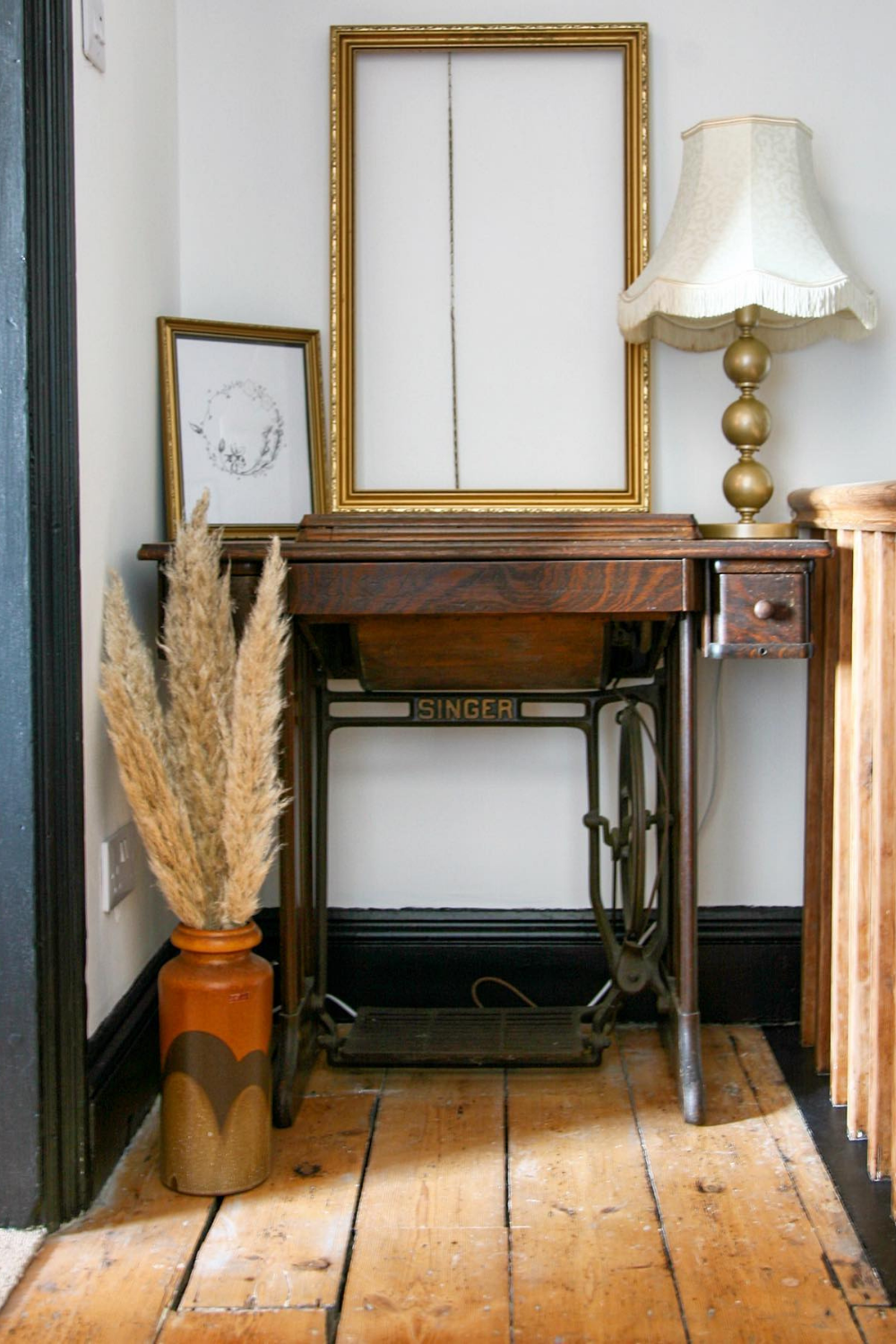 A singer sewing machine table with a gilt frame and lamp on top with a vase full of pampas grass in the foreground.