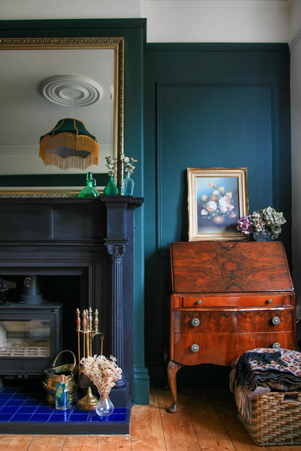 Buying Preloved or Vintage - a black fireplace with gold mirror and wood burner.  In the alcove there is a writing bureau with a vintage floral painting and flower frog filled with dried hydrangeas on top.