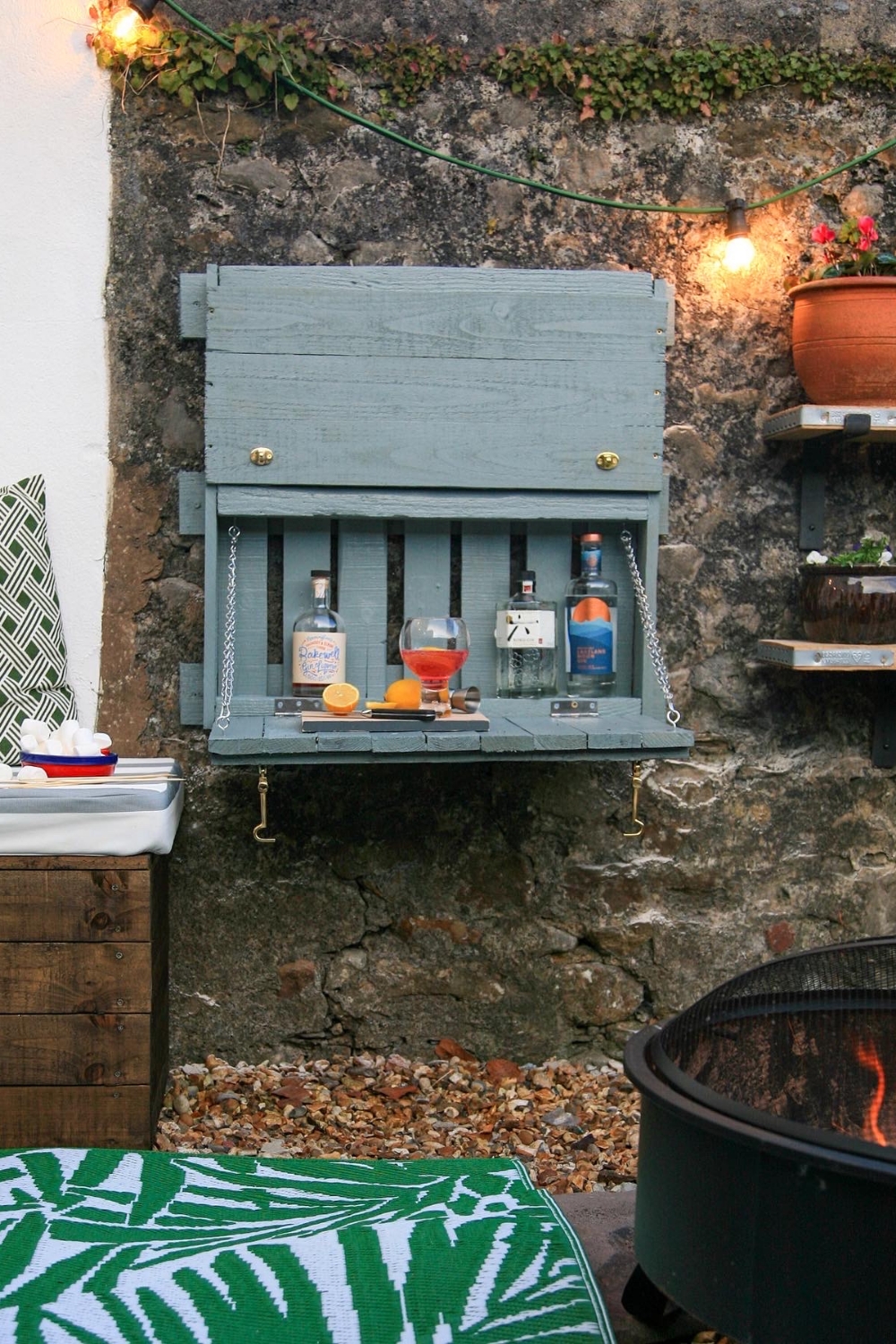 A drop leaf bar made from pallet wood showing three bottles of gin with lemon slices.  Painted in Wickes Dusky Pine Exterior Paint.  There is a fire pit in the foreground