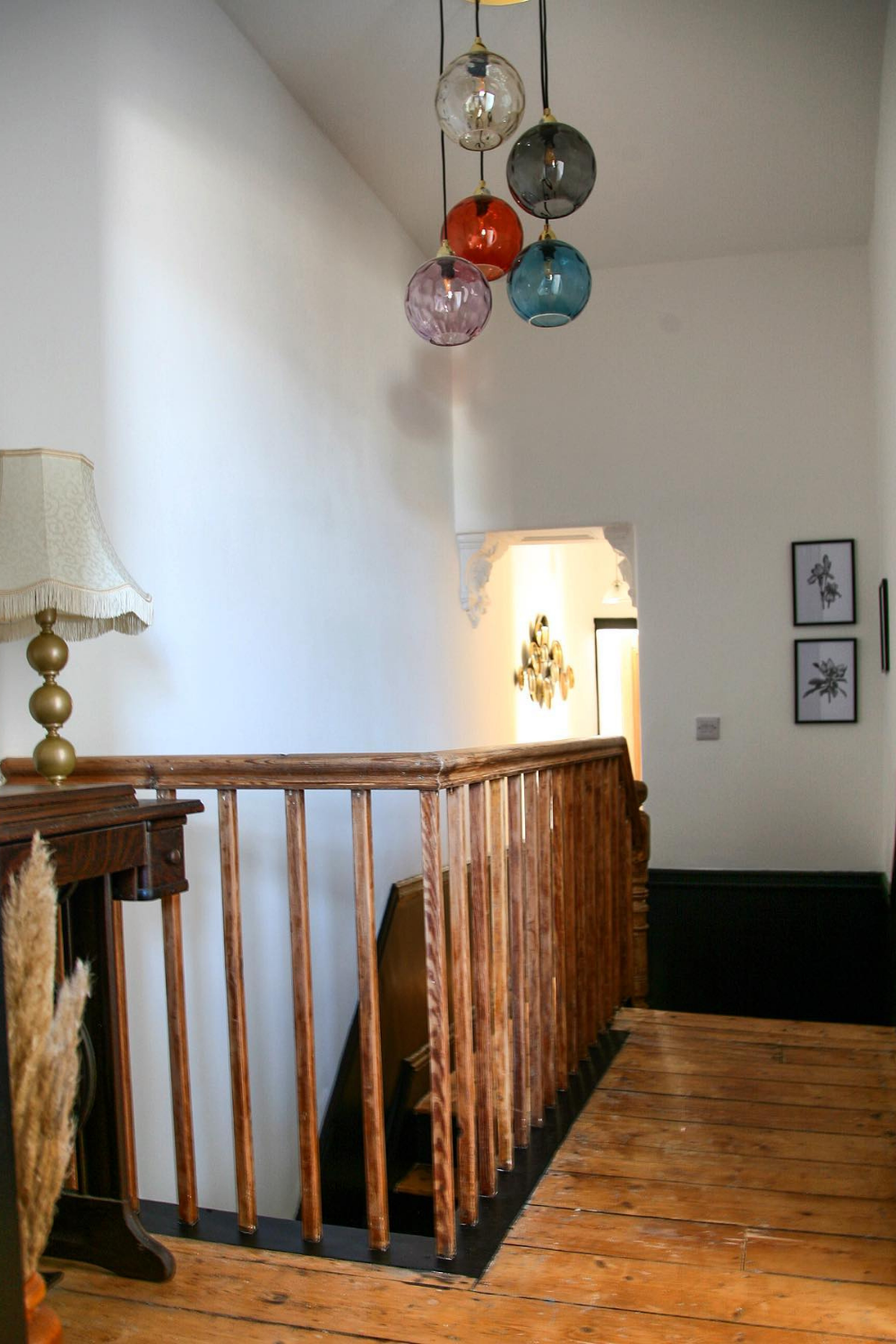 10 DIY Projects in Lockdown - landing area with wooden floorboards and a light fitting showing five glass light shades against white bare walls.