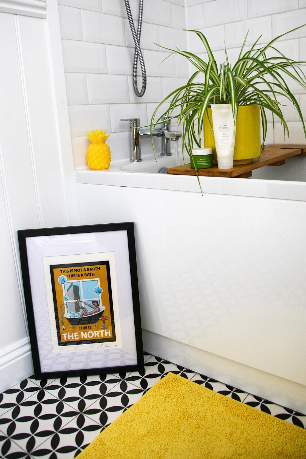 10 DIY Projects in Lockdown - a white bath with white metro tiles showing a bath board with a spider plant on toiletries on it.