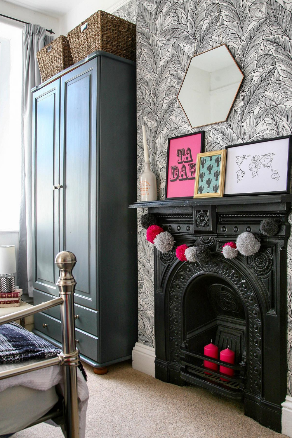 10 DIY Projects in Lockdown - a black fireplace with leaf wallpaper and bright pink pom pom accessories.