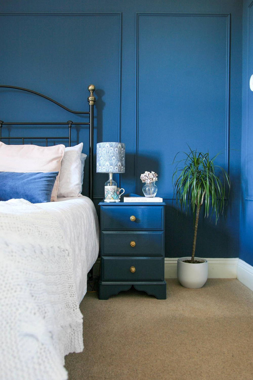 Image shows a bedside table with wall panelling behind using decorative moulding.