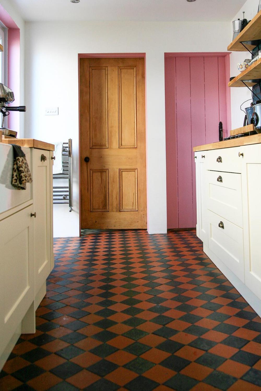 10 DIY Projects in Lockdown - a view of the kitchen showing pink door, original door, white kitchen cabinets and original tiled floor.